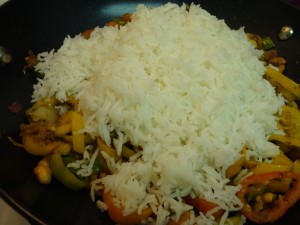 adding rice to cooked pepers